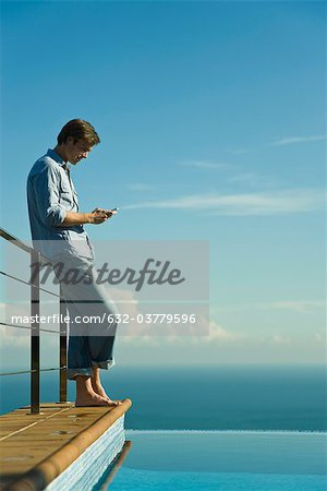 Man standing beside infinity pool, text messaging with cell phone Stock Photo - Premium Royalty-Free, Image code: 632-03779596