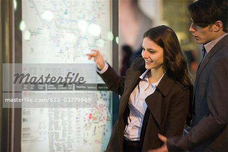 Couple looking at subway map Stock Photo - Premium Royalty-Free, Image code: 632-03779669