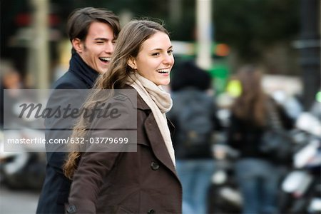 Young couple laughing and walking together outdoors Stock Photo - Premium Royalty-Free, Image code: 632-03779699
