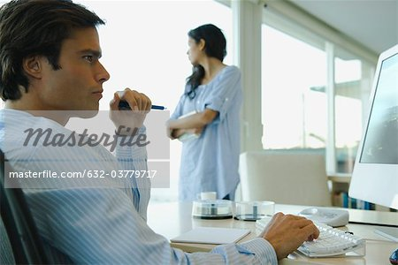 Man working on computer at home Stock Photo - Premium Royalty-Free, Image code: 632-03779717