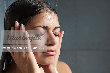 Woman washing face in shower Stock Photo - Premium Royalty-Free, Image code: 632-03847709