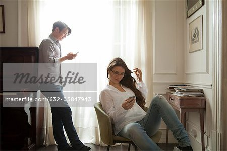 Couple text messaging at home Stock Photo - Premium Royalty-Free, Image code: 632-03847943
