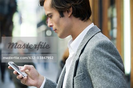 Man text messaging outdoors Stock Photo - Premium Royalty-Free, Image code: 632-03847952