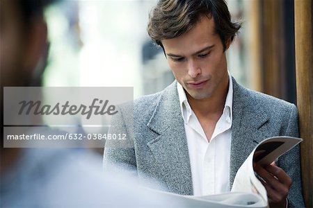 Man leaning against wall reading newspaper Stock Photo - Premium Royalty-Free, Image code: 632-03848012