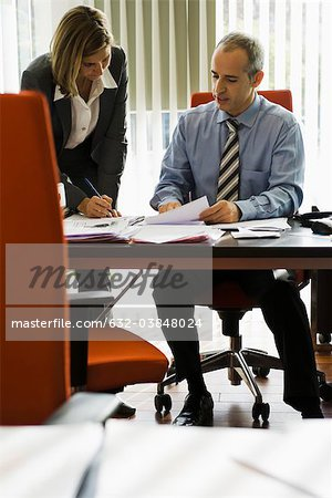 Businessman talking to female colleague as she making notes Stock Photo - Premium Royalty-Free, Image code: 632-03848024