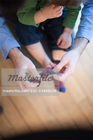 Father helping toddler put on socks, cropped Stock Photo - Premium Royalty-Free, Image code: 632-03848238