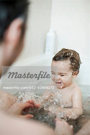 Toddler boy splashing in bath with his father Stock Photo - Premium Royalty-Free, Image code: 632-03848272