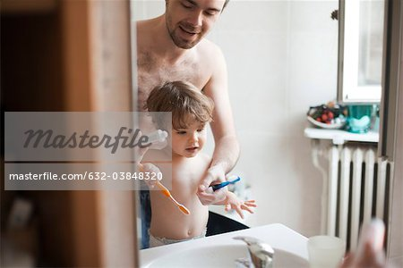Father and toddler son brushing their teeth together Stock Photo - Premium Royalty-Free, Image code: 632-03848320
