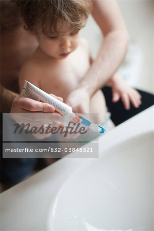 Father helping toddler son brush his teeth Stock Photo - Premium Royalty-Free, Image code: 632-03848321