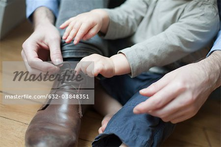 Chhild helping father tie shoelace Stock Photo - Premium Royalty-Free, Image code: 632-03848351