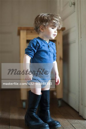 Toddler boy wearing father's boots Stock Photo - Premium Royalty-Free, Image code: 632-03848383