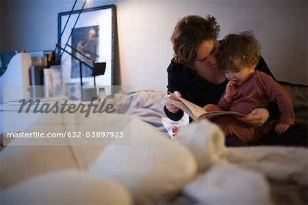 Mother holding toddler son on lap, reading bedtime story in bed Stock Photo - Premium Royalty-Free, Image code: 632-03897923