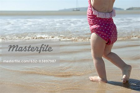 Toddler girl walking in surf at the beach, low section Stock Photo - Premium Royalty-Free, Image code: 632-03897987