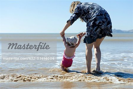 Mother and baby daughter walking in surf at the beach, rear view Stock Photo - Premium Royalty-Free, Image code: 632-03898006