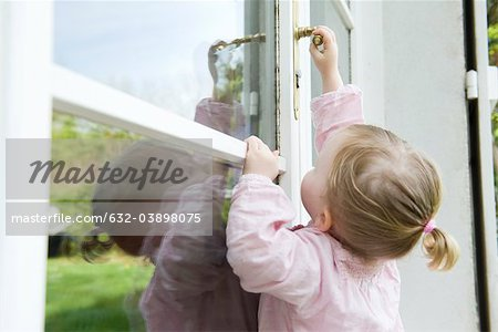Toddler girl reaching to open door Stock Photo - Premium Royalty-Free, Image code: 632-03898075