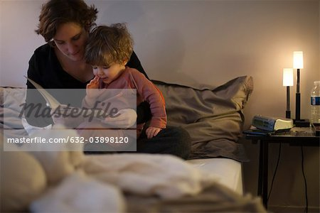 Mother holding toddler son on lap, reading bedtime story in bed Stock Photo - Premium Royalty-Free, Image code: 632-03898120