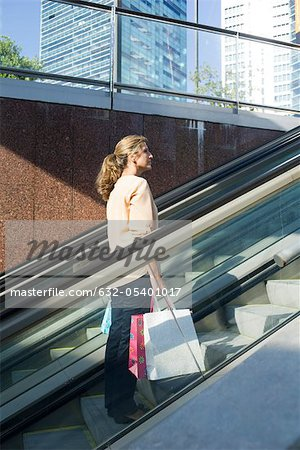 Woman carrying shopping bags going up on escalator outdoors Stock Photo - Premium Royalty-Free, Image code: 632-05401017