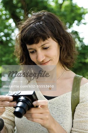 Woman looking at digital camera Stock Photo - Premium Royalty-Free, Image code: 632-05553600