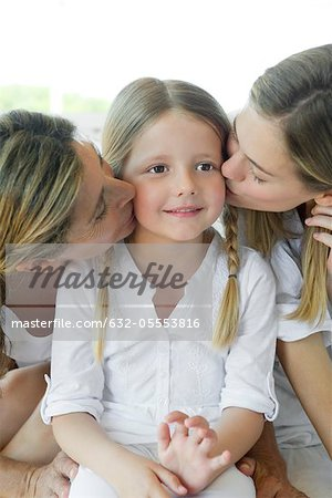 Girl being kissed on cheek by mother and grandmother Stock Photo - Premium Royalty-Free, Image code: 632-05553816