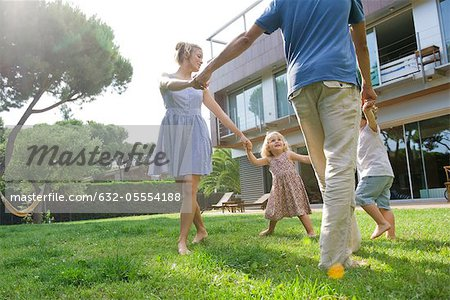 Family playing ring-around-the-rosy outdoors Stock Photo - Premium Royalty-Free, Image code: 632-05554188