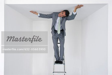 Executive standing on stepladder, pushing ceiling Stock Photo - Premium Royalty-Free, Image code: 632-05603993