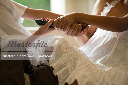 Children fighting over remote control, cropped Stock Photo - Premium Royalty-Free, Image code: 632-05604234