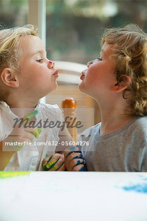 Little girl and boy looking at each other and puckering lips Stock Photo - Premium Royalty-Free, Image code: 632-05604276