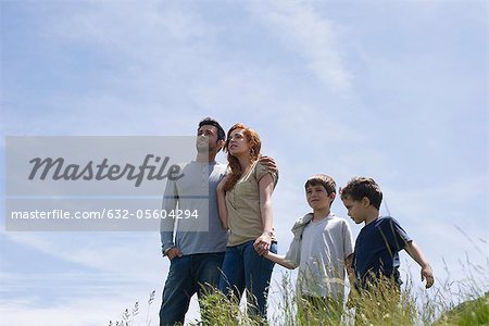 Parents and two boys standing on meadow holding hands, low angle view Stock Photo - Premium Royalty-Free, Image code: 632-05604294