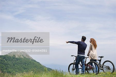 Couple standing by mountain bikes enjoying scenic mountain view Stock Photo - Premium Royalty-Free, Image code: 632-05604351