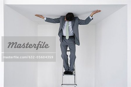 Executive standing on stepladder, arms outstretched on ceiling Stock Photo - Premium Royalty-Free, Image code: 632-05604359