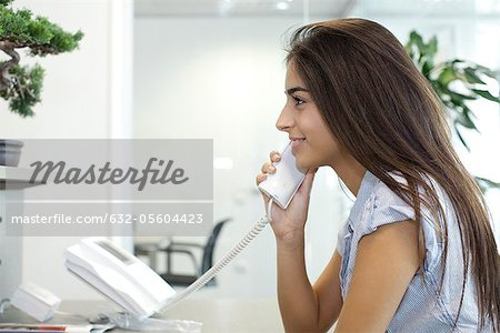 Woman talking on landline telephone Stock Photo - Premium Royalty-Free, Image code: 632-05604423