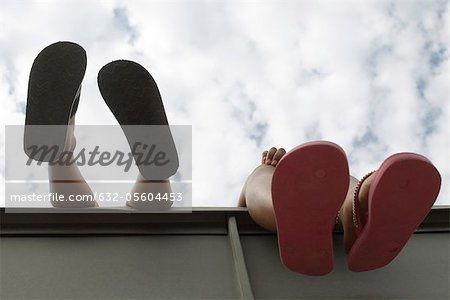 Children's feet dangling over ledge, low angle view Stock Photo - Premium Royalty-Free, Image code: 632-05604453