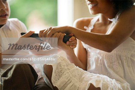 Children fighting over remote control, cropped Stock Photo - Premium Royalty-Free, Image code: 632-05604486