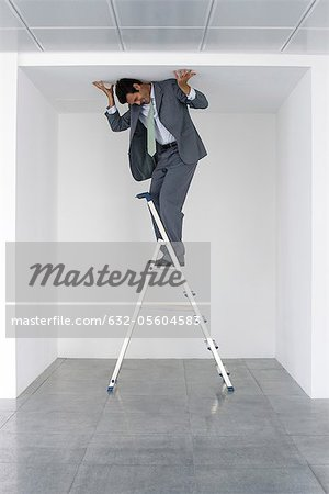 Executive standing on stepladder, pushing ceiling