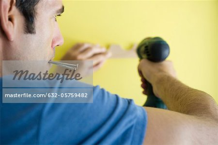 Man using power drill, biting screws in mouth Stock Photo - Premium Royalty-Free, Image code: 632-05759482