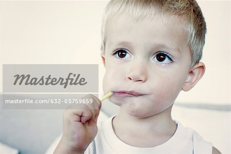 Little boy eating lollipop, portrait Stock Photo - Premium Royalty-Free, Image code: 632-05759659