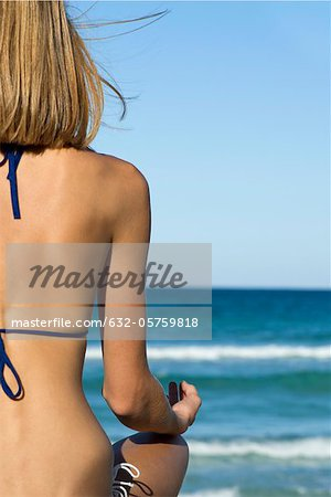Woman in bikini sitting in lotus position, rear view Stock Photo - Premium Royalty-Free, Image code: 632-05759818