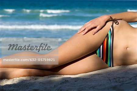 Woman in bikini lying on beach, low section Stock Photo - Premium Royalty-Free, Image code: 632-05759821
