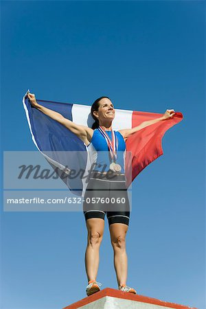 Female athlete on winner's podium, holding up French flag Stock Photo - Premium Royalty-Free, Image code: 632-05760060