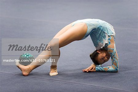Female gymnast performing floor routine with ball Stock Photo - Premium Royalty-Free, Image code: 632-05760121