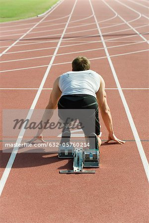 Runner crouched at startling line, rear view Stock Photo - Premium Royalty-Free, Image code: 632-05760214