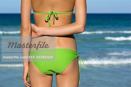 Woman in bikini standing by sea Stock Photo - Premium Royalty-Free, Image code: 632-05760324