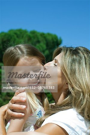 Mother kissing daughter's cheek Stock Photo - Premium Royalty-Free, Image code: 632-05760383