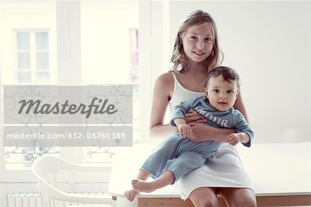 Girl holding baby sister on lap, portrait Stock Photo - Premium Royalty-Free, Image code: 632-05760388