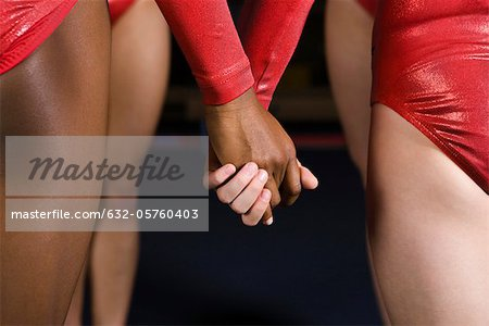 Female gymnasts holding hands, mid section Stock Photo - Premium Royalty-Free, Image code: 632-05760403