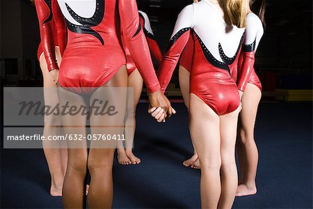 Group of female gymnasts holding hands in circle Stock Photo - Premium Royalty-Free, Image code: 632-05760411
