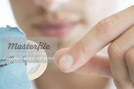 Man removing condom from wrapper, cropped Stock Photo - Premium Royalty-Free, Image code: 632-05760439