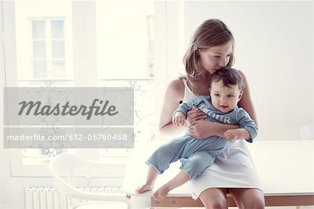 Girl kissing baby sister on lap, portrait Stock Photo - Premium Royalty-Free, Image code: 632-05760458