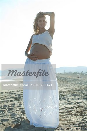 Pregnant woman standing on beach with hand on belly Stock Photo - Premium Royalty-Free, Image code: 632-05760471