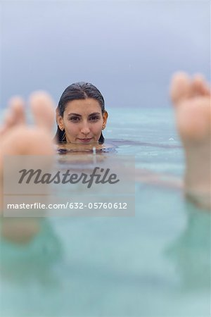 Woman floating in water, portrait Stock Photo - Premium Royalty-Free, Image code: 632-05760612